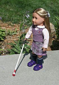 Une poupée blonde avec une canne blanche